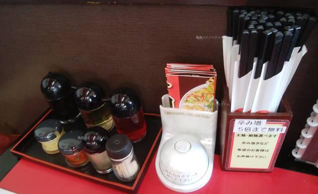 満里坂井店のテーブル上には卓上調味料やプラ箸が