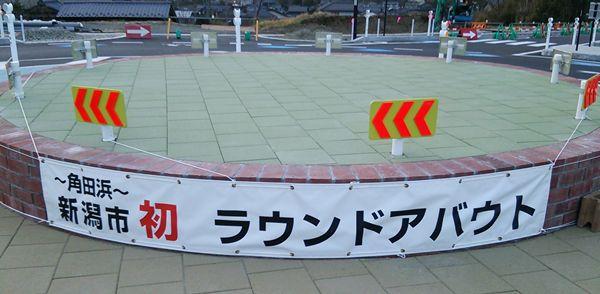 西蒲区角田浜のラウンドアバウトの中央にある、祝新潟市初ラウンドアバウトとかかれた帯