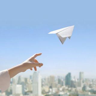 空に向かって紙飛行機を飛ばす小さい画像