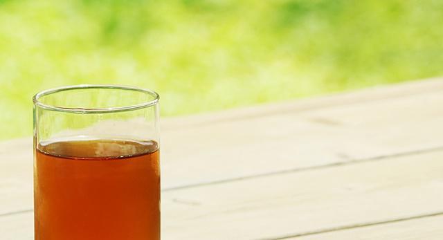 晴れた日の縁側に麦茶が入ったガラスのコップが置かれている