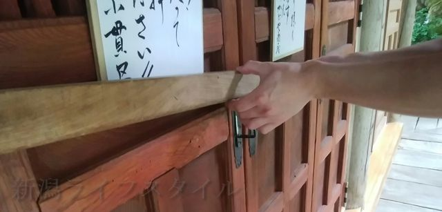 羽黒神社の社殿の扉のかんぬきを外す私の手