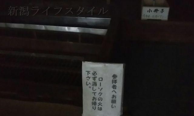 羽黒神社の社殿の中の、ローソクの火は消して行くようにという注意書きと、小冊子が置かれているらしい箱