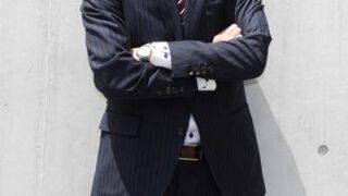 腕組みするスーツの男性