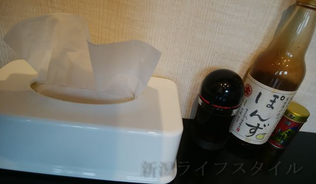 松兵衛の卓上にあるポン酢や醤油などの調味料とティッシュ