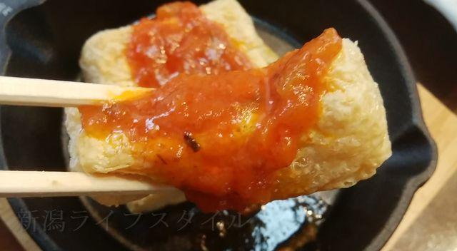 豆撰のオリーブオイルで揚げた油揚げトマトソースを一切れ持ち上げた図