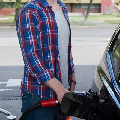 ガソリンスタンドで車に給油するチェックシャツにジーンズの男性