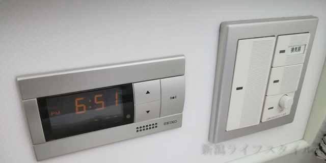 ホテルディアモント新潟西のベッド上部にある時計と電源スイッチ