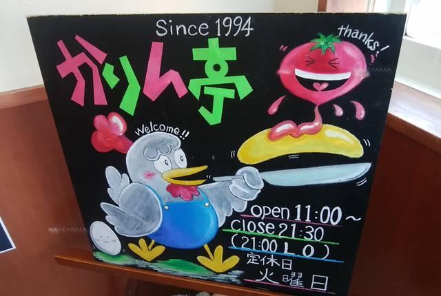 かりん亭の店頭にある営業時間やニワトリのイラストが描かれた黒板