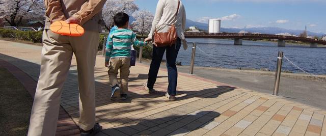 川べりの遊歩道を歩く親子孫3代