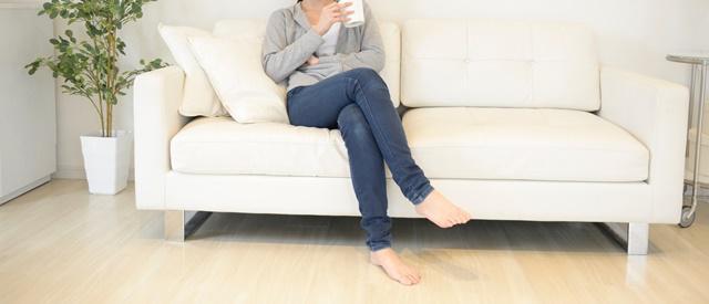 ソファーでコーヒーを飲みながらくつろぐ女性の首から下