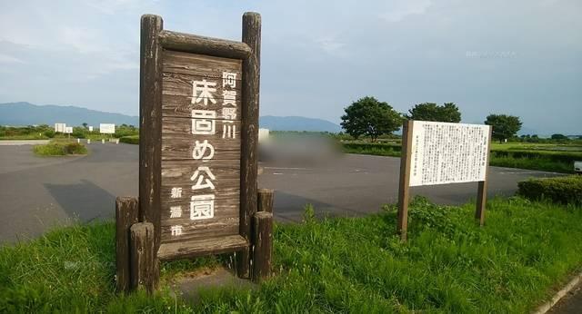 阿賀野川床固め公園の公園名の木製の看板とその後ろに見える駐車場と木々