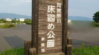 阿賀野川床固め公園の公園名が大きく書かれたログハウス調の看板のアップ