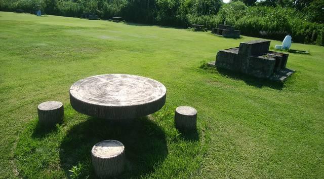 信濃バレー親水レクリエーション広場の芝生の上にテーブル・ベンチとかま場が斜めに並んだ図