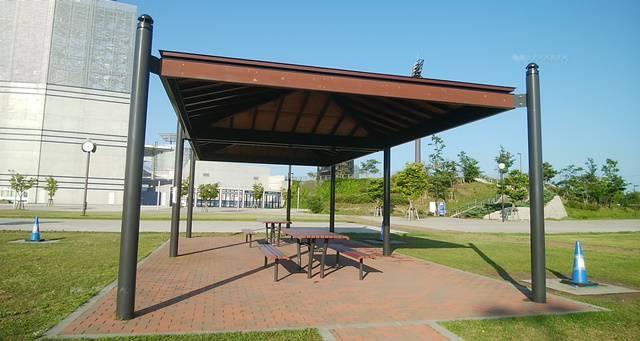 スポーツ公園バーベキュー場のあずまやとその中のテーブル・イス。そしてそばにあるバーベキューコンロ置き場