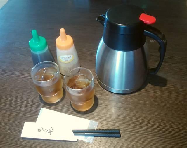 かつ平のドレッシングと、冷たいお茶とピッチャーと、紙おしぼりと箸