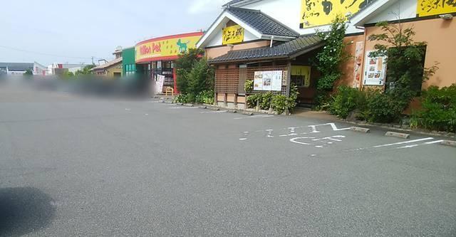 かつ平の駐車場の奥にお店の建物が斜めに映る。その奥にはmillion pet