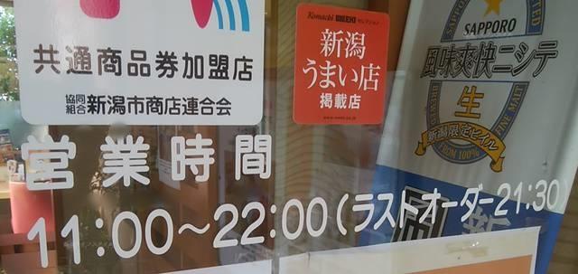 かつ平のウインドウに描かれた以前の平日・土日祝統一の11~22時という営業時間。新潟市共通商品券加盟店のシールも見える。