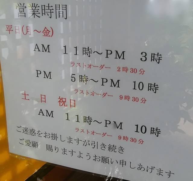 かつ平の営業時間の貼り紙。平日は11~15時、17~22時。土日祝は11~22時