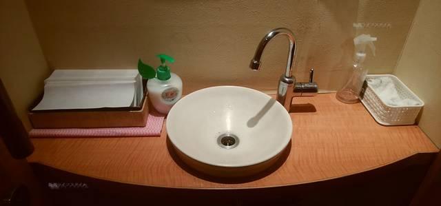 かつ平のトイレを出たところの手洗い場。木目で素敵な洗面台。ポンプ式のボトルのせっけん、紙タオル、除菌スプレーらしきもの、台ふきまで完備。