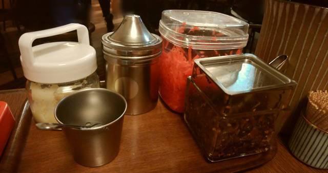 きんしゃい亭&麺やたぶきん赤道店の卓上の薬味。紅ショウガ、白ごま、すりおろしにんにく、高菜