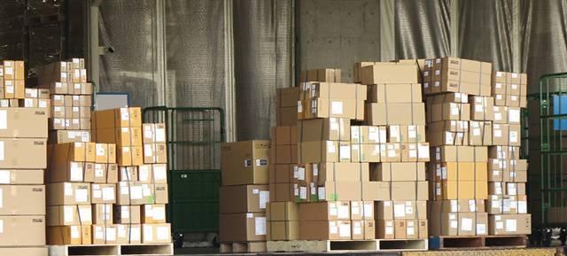 配送センターのコンクリートの床に山積みされた多数のダンボール箱