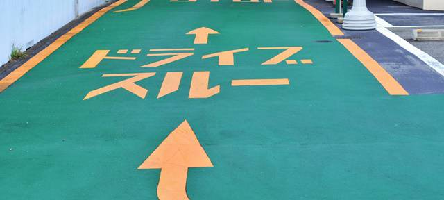 緑色に塗られた路面にオレンジ色でドライブスルーと書かれている
