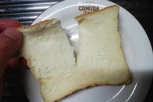 乃が美の食パンを半分にちぎる