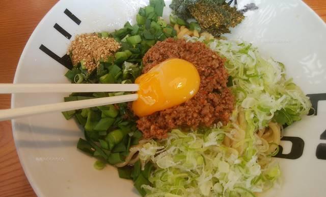 麺者風店小針店の辛肉まぜそばの生玉子に箸を刺す