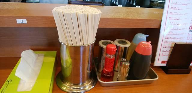フタツメ白根大通店の席に置かれた割りばしとティッシュ、胡椒などの調味料の数々