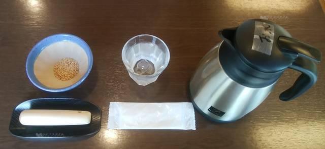テーブルの上に水、ピッチャー、紙おしぼり、白ごまが入った小さいすりばち、すりこぎ棒が置かれている