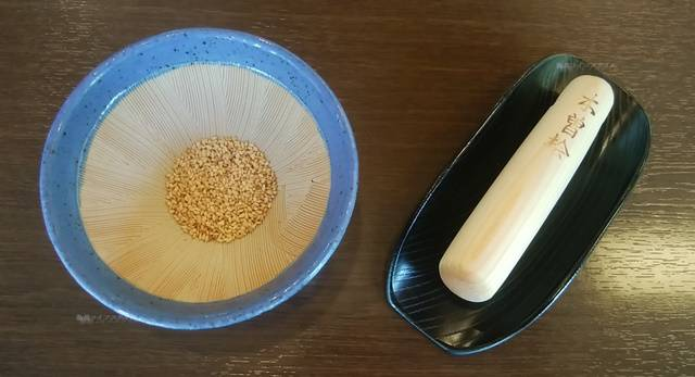 小さいすりばちに白ごまが大さじ2杯くらい入っており、よこに白木のすりこぎ棒が置かれている