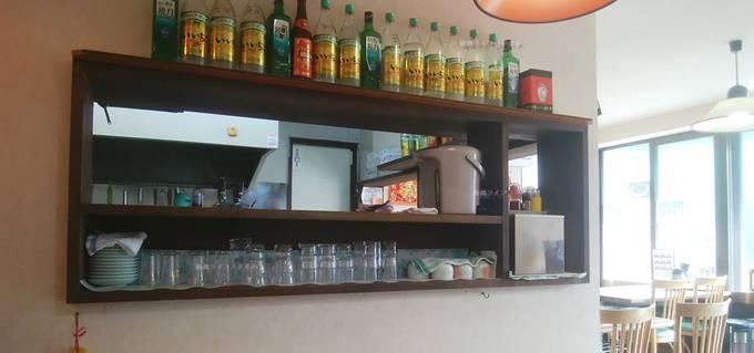 安家の厨房の対面式キッチン。上の方にはキープボトルが15本ほど並んでいる