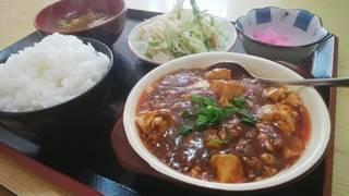 手前に麻婆豆腐、奥にごはん、みそ汁、サラダ、漬物が並ぶ定食