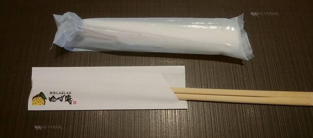 テーブルの上に置かれた紙おしぼりと割りばし