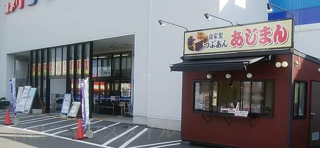 あじまん亀貝店の外観と隣のコメリパワーの入り口