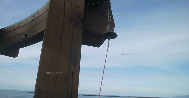 夕凪の橋の小さな幸せの鐘を横から見上げた様子