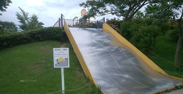 上堰潟公園の幅広の大きな滑り台を丘の下から見る