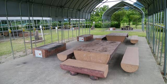 上堰潟公園のバーベキューの屋根の中にテーブルとベンチが並び、横にかま場がある
