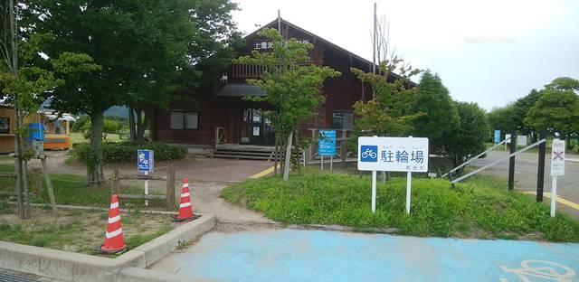 上堰潟公園の休憩所の建物の全体像と駐車場の看板が入った様子