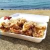 海辺のコンクリートの岸壁にからあげ酒場コウシのから揚げ弁当が置かれている